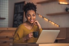Afro American girl in cafe. Beautiful Afro American girl in casual clothes is drinking coffee, looking at camera and smiling while working with a laptop in cafe royalty free stock photo