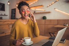 Afro American girl in cafe. Beautiful Afro American girl in casual clothes and glasses is drinking coffee, talking on the mobile phone and smiling while working royalty free stock photo