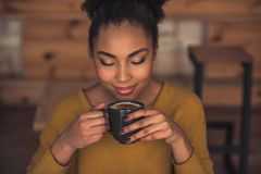 Afro American girl in cafe. Beautiful Afro American girl in casual clothes is smelling coffee and smiling while resting in cafe stock photography