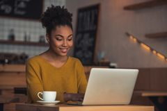 Afro American girl in cafe. Beautiful Afro American girl in casual clothes is using a laptop and smiling while sitting in cafe stock images