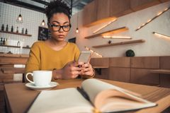 Afro American girl in cafe. Beautiful pensive Afro American girl in casual clothes and glasses is using a smart phone while studying in the cafe stock photo