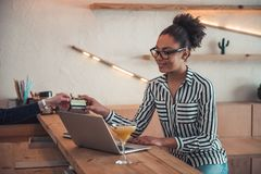 Afro American girl in cafe. Beautiful Afro American girl in smart casual clothes and glasses is giving a credit card and smiling while working with a laptop in royalty free stock image