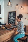 Afro American girl in cafe. Beautiful Afro American girl in smart casual clothes and glasses is giving a credit card while working with a laptop in cafe royalty free stock photos