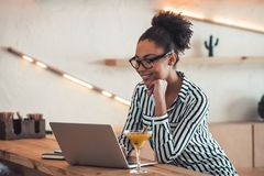 Afro American girl in cafe. Beautiful Afro American girl in smart casual clothes and glasses is smiling while working with a laptop in cafe stock images
