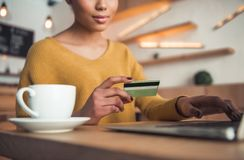 Afro American girl in cafe. Cropped image of beautiful Afro American girl drinking coffee and holding a credit card while paying online with a laptop in cafe stock photography