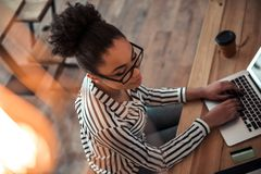 Afro American girl in cafe. High angle view of beautiful Afro American girl in smart casual clothes and glasses working with a laptop in cafe stock photography