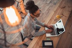 Afro American girl in cafe. High angle view of beautiful Afro American girl in smart casual clothes and glasses working with a laptop in cafe royalty free stock photo