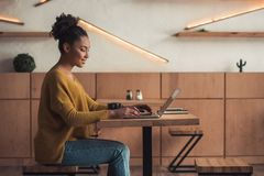 Afro American girl in cafe. Side view of beautiful Afro American girl in casual clothes smiling while working with a laptop in cafe royalty free stock image