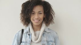 Afro American girl in casual clothes is looking at camera and smiling stock video