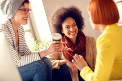 Afro-American girl with colleagues in firm chatting. Afro-American girl with female colleagues in firm chatting on pause from job royalty free stock photos