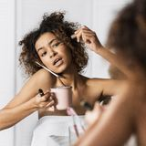 Sorry, I am late today concept. Afro-american girl in hurry put on makeup, drinking coffee and talking by phone simultaneously in front of mirror in bathroom stock photography