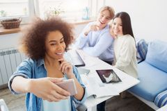 Afro american girl is taking a selfie of herself and her friends which are sitting at the table. All of them are posing royalty free stock photography