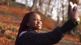 The afro-american girl is touching the hair and taking selfie in the autumn park. stock footage