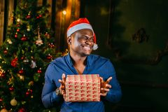 Afro american guy with charming smile holding Christmas gift in hands. Afro american guy with charming smile holding Christmas gift in his hands Royalty Free Stock Photos