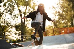 Afro american guy jumping with his skate. And performing a trick Royalty Free Stock Photography
