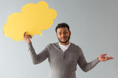 Afro American guy with speech bubble. Handsome Afro American guy is holding a speech bubble and lifting hand in dismay, on gray background royalty free stock photos