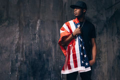 Afro american guy with US flag on dark background. Patriot, national event celebration, independence day, immigration, usa citizen concept Stock Image