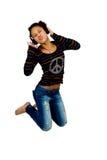 Afro american jump listening musicheadphones Stock Photography
