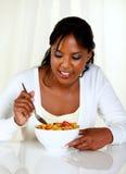 Afro-american kvinna som äter en bunke av sädesslag Arkivbild