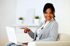 Afro-american kvinna som pekar till bärbar datorskärmen Arkivfoto