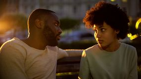 Afro-american lady looking at boyfriend with hope, misunderstanding, conflict stock images