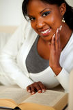 Afro-american lady smiling and reading a book Royalty Free Stock Images