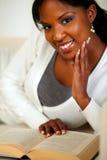 Afro-american lady som ler och läser en bok Royaltyfria Bilder