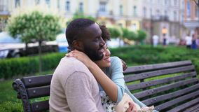 Afro-american loving couple nuzzling on bench, enjoying summer day together. Stock footage stock footage