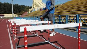 Afro-american male model runs with obstacles in the stadium. stock footage
