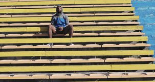 Afro-American male model sits on the yellow stairs in the stadium. stock footage