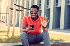 Afro american male in red t shirt texting sms on smartphone. Portrait of smiling african american male in a red polo t shirt Royalty Free Stock Image