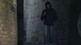 Afro-american male teen in hoodie feeling lonely walking abandoned city building. Stock footage stock footage