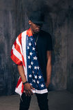 Afro american man with american flag. On dark background. Patriot, national event celebration, independence day, pride, usa citizen concept Stock Photo