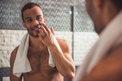 Afro American man in bathroom. Handsome naked Afro American man is applying cream on his face and smiling while looking into the mirror in bathroom Royalty Free Stock Photos