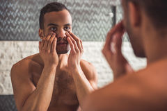 Afro American man in bathroom. Handsome naked Afro American man is examining his face while looking into the mirror in bathroom Royalty Free Stock Photo
