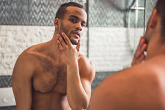 Afro American man in bathroom. Handsome naked Afro American man is examining his face while looking into the mirror in bathroom Stock Photography