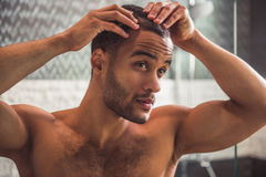 Afro American man in bathroom. Handsome naked Afro American man is examining his hair while looking into the mirror in bathroom Stock Image