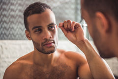 Afro American man in bathroom. Handsome naked Afro American man is plucking eyebrows while looking into the mirror in bathroom Stock Photo