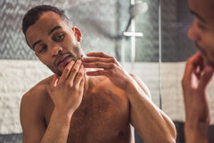 Afro American man in bathroom. Handsome naked Afro American man is squeezing pimples on his face while looking into the mirror in bathroom Royalty Free Stock Photo