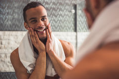 Afro American man in bathroom. Handsome naked Afro American man is touching his face and smiling while looking into the mirror in bathroom Royalty Free Stock Photos