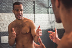 Afro American man in bathroom. Handsome naked Afro American man is winking at himself while looking into the mirror in bathroom Stock Images