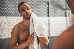 Afro American man in bathroom. Handsome naked Afro American man is wiping his face using a towel while looking into the mirror in bathroom Royalty Free Stock Photography