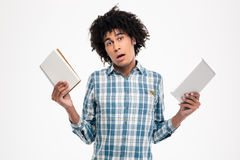 Afro american man choosing between paper book or tablet computer Royalty Free Stock Photo