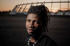 Afro-american man with dreadlocks with meditative look and steel earing. Stylish afro-american man with dreadlocks with meditative look and steel earing smiling Stock Image