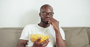 Man Watching TV. Afro-american man dressed in white shirt and eyeglasses eating snacks while watching TV, home leisure concept stock video footage