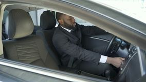 Afro-American man in expensive suit fastening and turning on ignition of his car. Stock footage stock footage