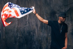 Afro american man hold in hand flying US flag. On dark background. Patriot, national event celebration, pride, usa citizen concept Stock Photos