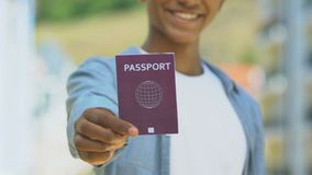 Afro-american man holding red passport, migration policy, simplified visa regime. Stock footage stock footage