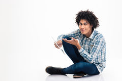 Afro american man holding tablet computer. Portrait of a happy afro american man sitting on the floor with tablet computer isolated on a white background Stock Photography
