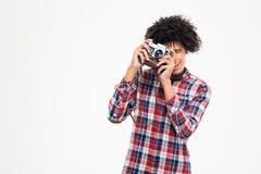 Afro american man making photo on retro camera Stock Photos